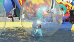 Schollen des kleinen Mädchens innerhalb des großen aufblasbaren Balls stock video
