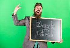Schommel deze school Het het onderwijsberoep eist talent en ervaring De leraar heet studenten welkom terwijl bord houdt stock afbeeldingen