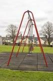 Schommeling bij een speelplaats van kinderen Stock Foto