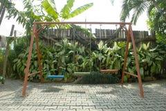 Schommeling in de groene tuin Royalty-vrije Stock Afbeeldingen
