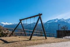 Schommeling, de speelplaats van het kind, bergmening, de sneeuw behandelde bergen van Alpen stock fotografie