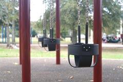 Schommeling in de speelplaats van kinderen royalty-vrije stock foto