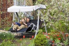 Schommeling in een bloeiende tuin Stock Afbeelding