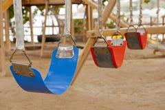 Schommeling in een speelplaats van kinderen Stock Afbeelding