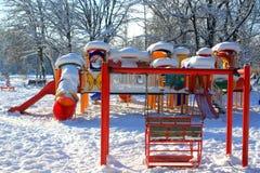 Schommeling en speelplaats met sneeuw wordt behandeld die Stock Afbeelding