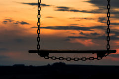 Schommeling en zonsondergang Stock Foto's