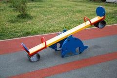 Schommelings heldere kleur in de vorm van een Dolfijn op de Speelplaats met met rubber bekleede oppervlakte stock afbeelding