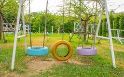 Schommelingsstoelen van oude banden voor kinderen in park worden gemaakt dat stock fotografie