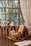 Schommelstoel dichtbij venster in ruimte met houten muren en vloer Stock Afbeelding