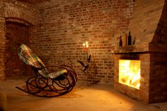 Schommelstoel door de open haard in baksteenruimte stock fotografie