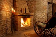 Schommelstoel door de open haard en met kaarsen royalty-vrije stock foto