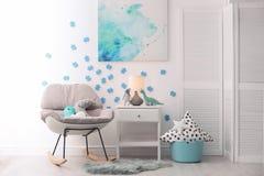 Schommelstoel en nightstand in babyruimte stock afbeelding