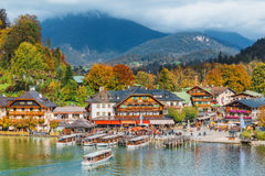 Schonau am Konigssee, Germany. A sightseeing boat cruising on Konigssee ( King's Lake ). Surrounded by colorful autumn trees and boathouses on a sunny morning~ royalty free stock photos
