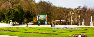 Schonbrunn zoo entrance and people walking around. Vienna, Austria - April 3, 2015: Schonbrunn zoo entrance gate with the advertisement billboards, part of the Stock Photography