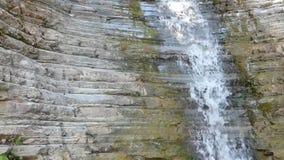 Schone waterdaling van oude rotsen - waterval op steenmuur stock footage