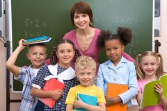 At school. Line of smart classmates looking at camera with happy teacher behind them Royalty Free Stock Photo