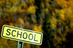 School. Yellow road sign for school with autumn colors in background Royalty Free Stock Images