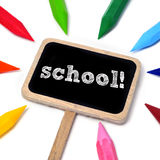 School. Word school written on a blackboard and some crayons of different colors on a white background Royalty Free Stock Photos