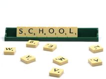 School. Scrabble letters spelling school with a white backround stock images