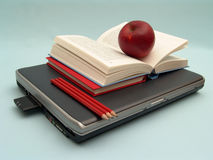 At school. Laptop with stack of books, red apple and red pencils on blue background Stock Images