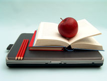 At school. Laptop with stack of books, red apple and red pencils on blue background Royalty Free Stock Photo