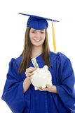 Caucasian teenager wearing blue graduation gown and holding piggy bank Royalty Free Stock Photo