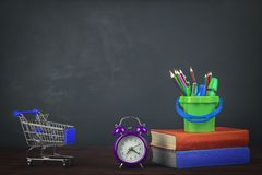 Stack of colorful textbooks on a wooden table, and grocery cart, stationery and alarm clock. Back to school. Stock Photos