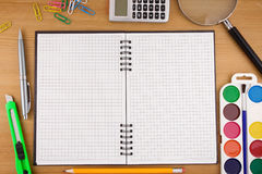 School accessories and checked notebook on wood Royalty Free Stock Image
