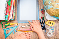School accessories on a desk. Top view of school accessories and blank tablet screen Stock Photography