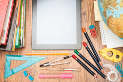 School accessories on a desk. Top view of school accessories and blank tablet screen Royalty Free Stock Image