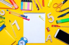 School accessories on a desk on a yellow background. concept of education. stationery. watches, colored pens, phone, markers. note stock photography