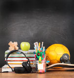 School accessories on desktop with blank blackboard in the backg Royalty Free Stock Images