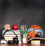 School accessories on desktop with blank blackboard in the backg Stock Photos