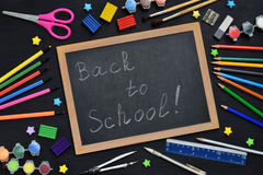 School accessories and supplies: pencils, markers, paints, pens, blackboard for inscriptions on a dark background. Back to school. Royalty Free Stock Image
