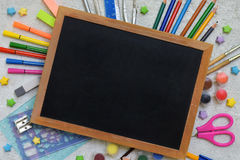 School accessories and supplies: pencils, markers, paints, pens, blackboard for inscriptions on a light background. Back to school. View from above. Flat lay stock photo