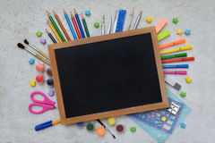 School accessories and supplies: pencils, markers, paints, pens, blackboard for inscriptions on a light background. Back to school Stock Photography
