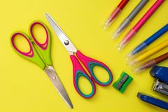 School accessories on a yellow background. Scissors, pens, sharpener, stapler.  stock photography
