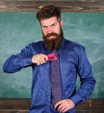 School accident prevention. School stationery. Man scruffy use stapler dangerous way. Hipster teacher formal wear. Necktie holds stapler. Teacher bearded man royalty free stock photography