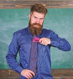 School accident prevention. School stationery. Man scruffy use stapler dangerous way. Hipster teacher formal wear. Necktie holds stapler. Teacher bearded man stock photo