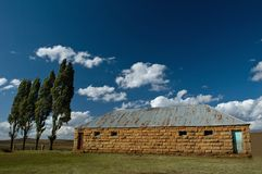 School in Africa. A sandstone school under a blue sky with white clouds Stock Photos