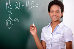 School. African American student doing math problems on the chalkboard Royalty Free Stock Photography