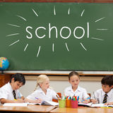 School against cute pupils sitting at desk Stock Photography