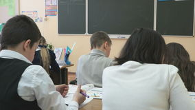 School-age children sit at school desks on lesson stock video