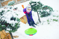 School age girl working with shovel in winter snowy yard Stock Photo