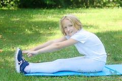 School-age jong geitjemeisje in lichte kleren neemt sportoefening op een mat in het park In openlucht training Stock Afbeeldingen