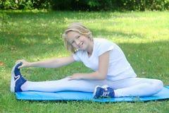 School-age jong geitjemeisje in lichte kleren neemt sportoefening op een mat in het park In openlucht training Royalty-vrije Stock Afbeeldingen
