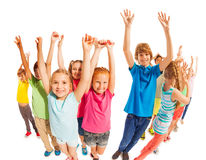 School age kids stand together with raised hands. Many happy school age kids stand together with raised hands isolated on white stock photography