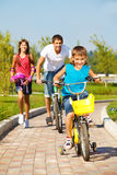 School aged boy and his father cycling Stock Photo