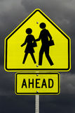 School ahead(with clipping path). A yellow school ahead sign with post and screws and dark rain clouds Royalty Free Stock Image
