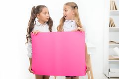 School announcement concept. Surprising news. Girls hold announcement banner. Girls kids holding paper banner for. Announcement. Children surprised with blank stock photos